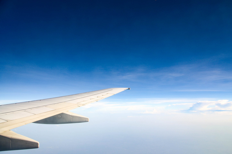 wing of a plan, flying in a blue sky with low clouds