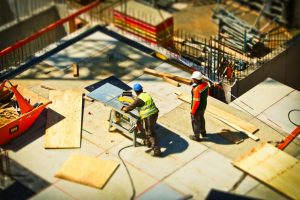 Two people at with pine sheets at a construction site one man using a circle saw
