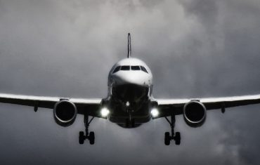 plane flying in dark cloudy sky