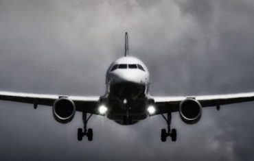 plane flying in dark cloudy sky