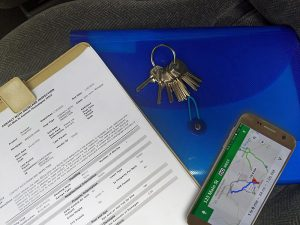 Inspection clipboard with plastic binder, keys and phone with location directions map